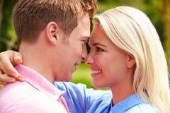 Pares jovenes románticos que abrazan en jardín Imagen de archivo