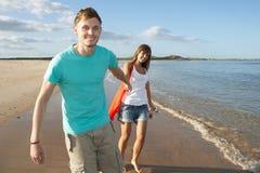 Pares jovenes románticos que recorren a lo largo de línea de la playa Fotos de archivo libres de regalías