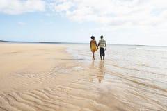 Pares jovenes románticos que recorren a lo largo de línea de la playa Imagen de archivo