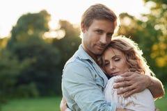 Pares jovenes románticos que se abrazan en la puesta del sol Fotos de archivo