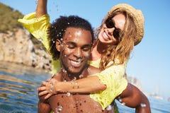 Pares jovenes románticos que se divierten en el mar junto Imagen de archivo