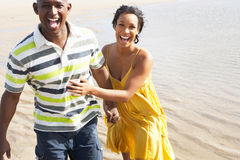 Pares jovenes románticos que se ejecutan a lo largo de línea de la playa Foto de archivo