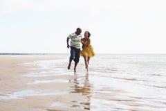 Pares jovenes románticos que se ejecutan a lo largo de línea de la playa Fotos de archivo