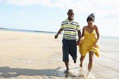Pares jovenes románticos que se ejecutan a lo largo de línea de la playa Imagen de archivo libre de regalías