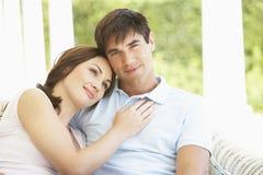 Pares jovenes románticos que se relajan junto en banco exterior fotos de archivo libres de regalías