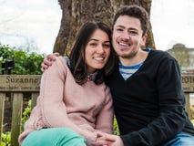 Pares jovenes románticos que se sientan en banco de parque junto Foto de archivo