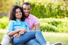 Pares jovenes románticos que se sientan en jardín Imagen de archivo libre de regalías