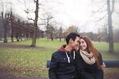 Pares jovenes románticos que se sientan en un banco de parque Fotos de archivo