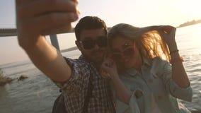 Pares jovenes románticos que sonríen y que toman su foto en smatphone almacen de video