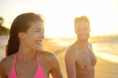Pares jovenes románticos sonrientes en puesta del sol de la playa Imágenes de archivo libres de regalías