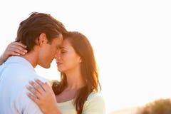 Pares jovenes románticos en amor en la puesta del sol Foto de archivo libre de regalías