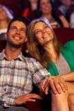 Pares jovenes románticos felices en cine Imagen de archivo libre de regalías