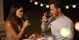 Pares jovenes románticos que gozan de la cena y del vino Foto de archivo libre de regalías