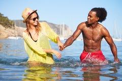 Pares jovenes románticos que se divierten en el mar junto Foto de archivo