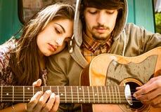 Pares jovenes románticos que tocan la guitarra al aire libre después de la lluvia Imágenes de archivo libres de regalías