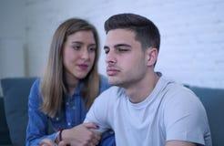 Pares jovenes 20s con el hombre triste y corazón quebrado deprimido y novia sufridores del dolor quizá que dan a su novio ayuda d Imagenes de archivo