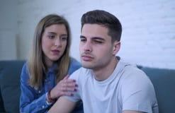 Pares jovenes 20s con el hombre triste y corazón quebrado deprimido y novia sufridores del dolor quizá que dan a su novio ayuda d Foto de archivo libre de regalías