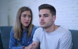 Pares jovenes 20s con el hombre triste y corazón quebrado deprimido y novia sufridores del dolor quizá que dan a su novio ayuda d Fotografía de archivo libre de regalías