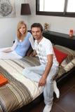 Pares jovenes sentados en cama Imagen de archivo libre de regalías