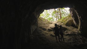 Pares jovenes: Siluetas Defocused de la gente con las linternas en la cueva