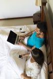 Pares jovenes Sit In Bed, hombre de la sonrisa feliz y mujer hispánicos que usa el ordenador portátil elegante del teléfono de la Fotografía de archivo