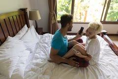 Pares jovenes Sit On Bed, hombre de la sonrisa feliz y mujer hispánicos que usa el teléfono de Smart de la célula Foto de archivo libre de regalías