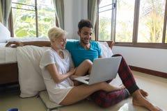 Pares jovenes Sit Near Bed, hombre de la sonrisa feliz y mujer hispánicos que usa el ordenador portátil Fotografía de archivo