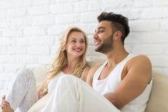 Pares jovenes Sit On Pillows Floor, hombre de la sonrisa feliz y amantes hispánicos de la mujer en dormitorio Foto de archivo libre de regalías