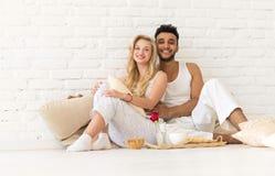 Pares jovenes Sit On Pillows Floor, hombre hispánico feliz y desayuno Tray Lovers In Bedroom de la mujer Fotos de archivo libres de regalías