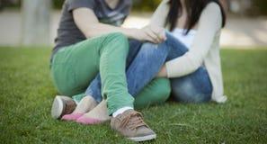 Pares jovenes sitted en la hierba Imagen de archivo