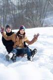 Pares jovenes sledding en nieve foto de archivo