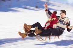 Pares jovenes Sledding y que gozan en Sunny Winter Day imagenes de archivo