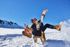 Pares jovenes Sledding y que gozan en Sunny Winter Day Imagenes de archivo