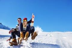 Pares jovenes Sledding y que gozan en Sunny Winter Day Imagen de archivo libre de regalías