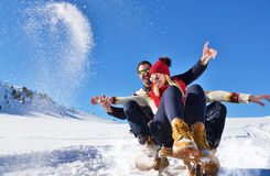 Pares jovenes Sledding y que gozan en Sunny Winter Day Imagen de archivo