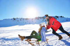 Pares jovenes Sledding y que gozan en Sunny Winter Day foto de archivo
