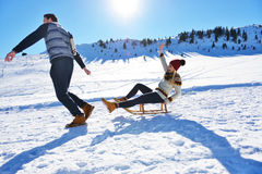 Pares jovenes Sledding y que gozan en Sunny Winter Day fotos de archivo