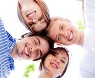Pares jovenes sonrientes con el cielo claro Imagenes de archivo