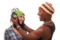 Pares jovenes sonrientes con los auriculares grandes Imágenes de archivo libres de regalías
