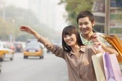 Pares jovenes sonrientes con los bolsos de compras coloridos que granizan un taxi en la calle en Pekín, China Imagen de archivo libre de regalías