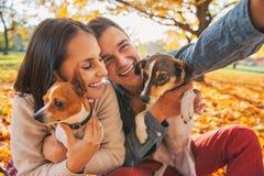 Pares jovenes sonrientes con los perros al aire libre que hacen el selfie imágenes de archivo libres de regalías