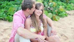 Pares jovenes sonrientes en amor, sentándose y abrazando en la playa almacen de metraje de vídeo