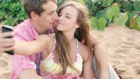 Pares jovenes sonrientes en el amor que toma el autorretrato con el teléfono de la cámara en la playa almacen de video