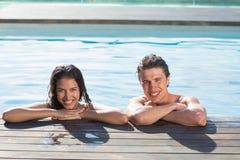 Pares jovenes sonrientes en piscina Imagen de archivo