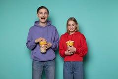 Pares jovenes sonrientes felices en la ropa casual que se opone a la pared azul con palomitas en manos fotos de archivo