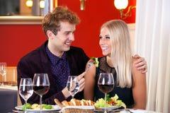 Pares jovenes sonrientes - Guy Feeding His Partner Foto de archivo libre de regalías
