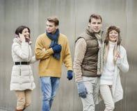 Pares jovenes sonrientes que caminan contra la pared Fotografía de archivo libre de regalías