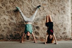 Pares jovenes sonrientes que hacen una posición de la posición del pino en una pared de piedra Foto de archivo