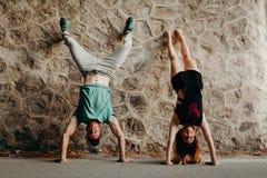 Pares jovenes sonrientes que hacen una posición de la posición del pino en una pared de piedra Fotografía de archivo libre de regalías