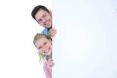 Pares jovenes sonrientes que ocultan detrás de una muestra en blanco Imágenes de archivo libres de regalías